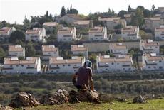 <p>Palestinien masqué face à la colonie juive de Halamish, en Cisjordanie. Au lendemain de la reconnaissance implicite à l'Onu d'un Etat palestinien, Israël a confirmé vendredi un projet de construction de quelque 3.000 nouvelles habitations pour ses colons en Cisjordanie et à Jérusalem-Est. /Photo prise le 30 novembre 2012/REUTERS/Mohamad Torokman</p>