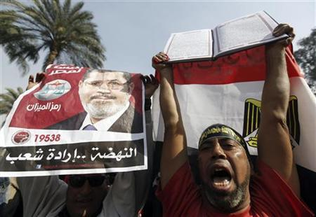 A supporter of Egyptian President Mohamed Mursi chants pro-Mursi slogans as he holds up a Koran during a rally in the vicinity of Cairo University and Nahdet Misr Square in Giza, on the outskirts of Cairo December 1, 2012. Tens of thousands of Islamists demonstrated in Cairo on Saturday in support of Mursi, who is racing through a constitution to try to defuse opposition fury over his newly expanded powers. REUTERS/Amr Abdallah Dalsh (EGYPT - Tags: POLITICS CIVIL UNREST RELIGION)