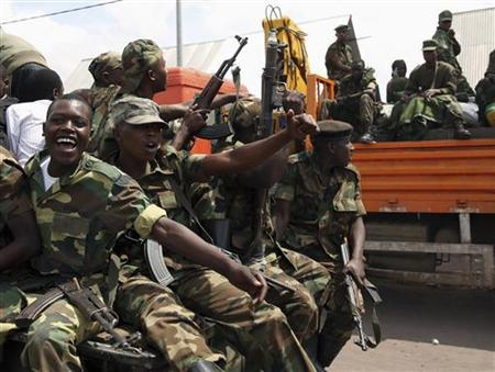M-23 rebel fighters are seen on trucks as they withdraw from Goma December 1, 2012. Rebel fighters, singing and brandishing weapons, pulled out of Democratic Republic of Congo's eastern border city of Goma on Saturday, raising hopes regional peace efforts could advance negotiations to end the insurgency. REUTERS/Goran Tomasevic (DEMOCRATIC REPUBLIC OF CONGO - Tags: CONFLICT POLITICS)
