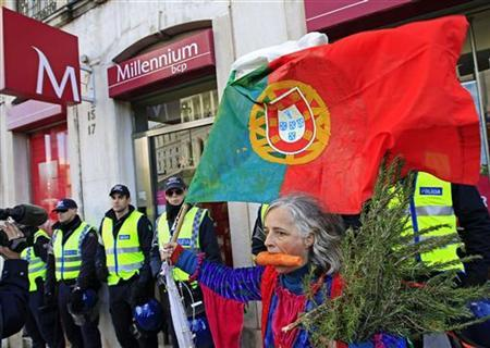 A woman protests in front of a bank guarded by policemen during an anti-austerity demonstration in front of Portugal's parliament in Lisbon November 27, 2012. Portugal's parliament gave final approval on Tuesday to a 2013 budget which promises a third year of recession and the biggest tax hikes in modern history to ensure international bailout terms are met. A few thousand protesters gathered outside parliament to oppose the bill, which far-left opposition lawmakers have promised to challenge in the country's constitutional court. REUTERS/Jose Manuel Ribeiro (PORTUGAL - Tags: POLITICS BUSINESS EMPLOYMENT CIVIL UNREST)