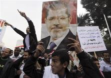 <p>Manifestation de soutien au président égyptien Mohamed Morsi, près de l'université du Caire. Le chef de l'Etat égyptien a fixé samedi au 15 décembre prochain la tenue du référendum sur le projet de constitution élaboré par l'Assemblée constituante mais les circonstances de sa rédaction ainsi qu'un décret élargissant dans l'immédiat les pouvoirs du président ont semé le trouble dans le pays où l'opposition laïque notamment redoute que cette constitution ne protège pas les libertés fondamentales. /Photo prise le 1er décembre 2012/REUTERS/Amr Abdallah Dalsh</p>