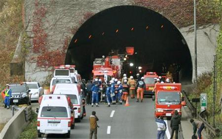 Police officers and firefighters gather in front of the Sasago Tunnel on the Chuo Expressway in Otsuki, Yamanashi prefecture, in this photo taken by Kyodo December 2, 2012. MANDATORY CREDIT. REUTERS/Kyodo FOR EDITORIAL USE ONLY. NOT FOR SALE FOR MARKETING OR ADVERTISING CAMPAIGNS. THIS IMAGE HAS BEEN SUPPLIED BY A THIRD PARTY. IT IS DISTRIBUTED, EXACTLY AS RECEIVED BY REUTERS, AS A SERVICE TO CLIENTS. MANDATORY CREDIT. JAPAN OUT. NO COMMERCIAL OR EDITORIAL SALES IN JAPAN
