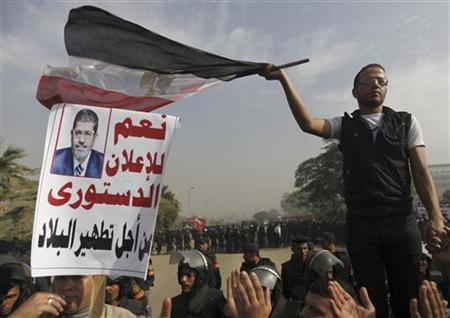 A supporter of Egyptian President Mohamed Mursi waves an Egyptian national flag in front of the Supreme Constitutional Court in Maadi, south of Cairo December 2, 2012. REUTERS/Amr Abdallah Dalsh