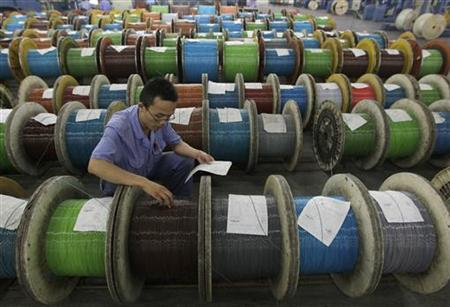 An employee inspects the newly-made optical cables at a factory in Wuhan, Hubei province July 25, 2012. REUTERS/Stringer/Files