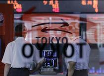 Посетители Токийской фондовой биржи смотрят на экраны с котировками 13 июля 2012 года. Фондовые рынки Японии и Южной Кореи выросли в понедельник благодаря слабой иене и высоким экономическим показателям Китая, а рынки Гонконга и Китая снизились из-за фиксации прибыли. REUTERS/Toru Hanai