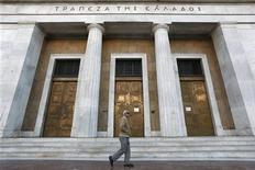 Мужчина проходит мимо здания Банка Греции в Афинах 9 ноября 2012 года. Экономика Греции может начать восстанавливаться быстрее, чем ожидается сейчас, если страна быстро проведет реформы, согласованные в рамках международной программы помощи, сообщил в понедельник Центробанк. REUTERS/Yorgos Karahalis