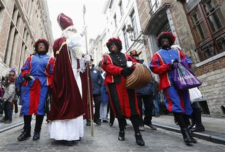 Saint Nicholas (2nd L) is escorted by his three assistants called 'Zwarte Piet' (Black Pete) during a traditional parade in central Brussels December 1, 2012. REUTERS-Francois Lenoir
