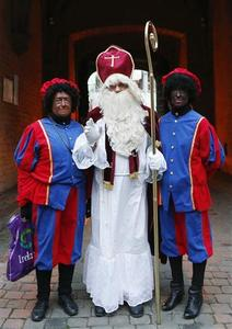 Saint Nicholas (C) poses with his two assistants called 'Zwarte Piet' (Black Pete) during a traditional parade in central Brussels December 1, 2012. REUTERS-Francois Lenoir