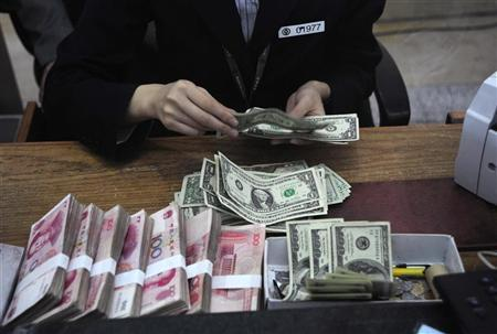 An employee checks U.S. dollar banknotes at a branch of Bank of China in Hefei, Anhui province November 2, 2009. said. REUTERS/Stringer/Files