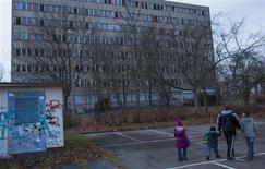 A man and three children walk past a disused workers dormitory in the steel town of Eisenhuettenstadt, 124 km (77 miles) east of Berlin November 26, 2012. Angela Merkel hopes for re-election next year as a reward for keeping the euro zone intact, but many people in the former East Germany where she grew up feel more like second-class citizens than good Europeans and may give her the cold shoulder. Income and jobs in the former German Democratic Republic still lag behind the west more than 20 years after reunification and trillions of euros in transfers have not stemmed an exodus that has left some areas looking like ghost towns. Picture taken November 26, 2012. TO GO WITH STORY GERMANY-EAST/ REUTERS/Thomas Peter