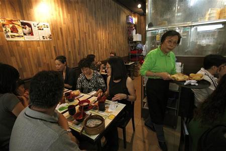 A waitress serves Baked BBQ Pork Cake at the Michelin-starred Tim Ho Wan in Hong Kong's Mong Kok November 27, 2009. REUTERS/Tyrone Siu