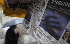 A man passes by a newspaper featuring the Euro currency sign in central Athens November 21, 2012. REUTERS/John Kolesidis