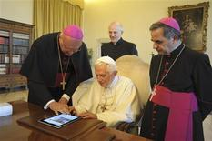 Pope Benedict XVI uses an iPad device at the Vatican in this file photo dated June 28, 2011. Pope Benedict's handle on Twitter will be @pontifex. REUTERS/Osservatore Romano