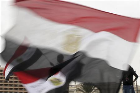 Anti-Mursi protesters, seen through Egyptian flags, chant anti-Mursi slogans in Tahrir square in Cairo December 4, 2012. REUTERS/Asmaa Waguih