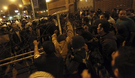Anti-Mursi protesters remove barbed wire during clashes with riot police in front of the presidential palace in Cairo, December 4, 2012. Egyptian police battled thousands of protesters outside President Mohamed Mursi's palace in Cairo on Tuesday, prompting the Islamist leader to leave the building, two presidential sources said. REUTERS/Amr Abdallah Dalsh