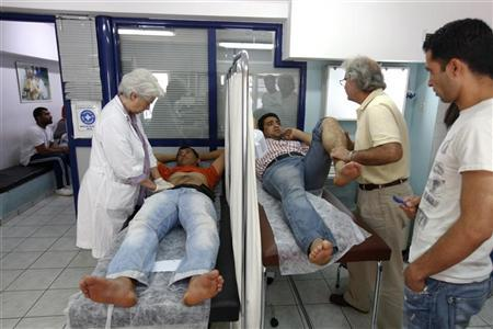 Doctors examine patients at a medical centre of the Greek delegation of the Doctors of the World in Athens May 31, 2012. REUTERS/Yorgos Karahalis
