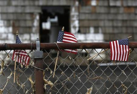 American flags are seen outside a home damaged from Hurricane Sandy in Lindenhurst, New York December 4, 2012. REUTERS/Shannon Stapleton
