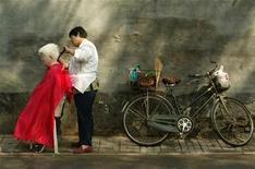 Мужчина стрижет пожилую женщину в Пекине 27 сентября 2002 года. Рост сектора услуг Китая замедлился в ноябре в результате медленного увеличения числа новых заказов, свидетельствует индекс менеджеров по закупкам для сектора услуг, рассчитываемый по заказу HSBC. REUTERS/Andrew Wong
