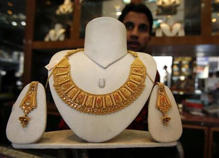 A shopkeeper displays gold jewellery inside his shop in Jammu October 17, 2008. REUTERS/Amit Gupta/Files