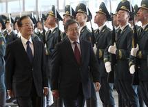 Премьеры Китая и Киргизии Вэнь Цзябао и Жанторо Сатыбалдиев осматривают строй почетного караула на официальной церемонии встречи в Бишкеке 4 декабря 2012 года. Китай пригласил страны Центральной Азии инвестировать в железные дороги, автотрассы и энергетику, используя кредиты на $10 миллиардов, которые позволят Пекину приблизиться к богатому ресурсами бывшему советскому региону. REUTERS/Vladimir Pirogov