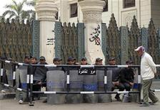 Um homem caminha em frente à tropa de choque no portão do palácio presidencial em Cairo, no Egito. 5/12/2012 REUTERS/Mohamed Abd El Ghany