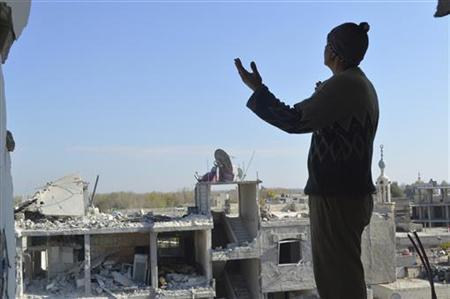 A man looks at buildings damaged by what activists said were missiles fired by a Syrian Air Force fighter jet loyal to President Bashar al-Assad at Jessreen area in Ghouta east of Damascus December 2, 2012. REUTERS/Karm Seif/Shaam News Network/Handout