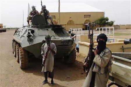 Fighters from the Al Qaeda-linked Islamist group MUJWA, who are travelling with a convoy including Burkina Faso foreign minister Djibril Bassole, stand guard in Gao, northern Mali, August 7, 2012. REUTERS/Stringer