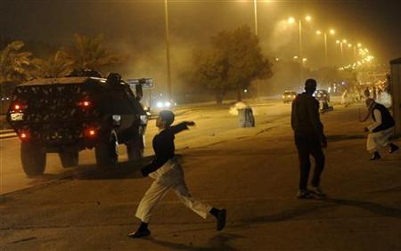 A boy throws stones at anti-riot police during clashes as demonstrators protest against the election results in Kuwait December 4, 2012. . REUTERS/Obaida al Ahmad