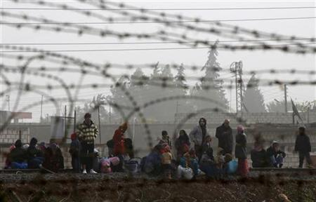 Syrians gather at a railway track as they try to cross the border from the Syrian town of Ras al-Ain to the Turkish border town of Ceylanpinar, Sanliurfa province December 4, 2012. REUTERS/Laszlo Balogh (TURKEY - Tags: POLITICS MILITARY CONFLICT)