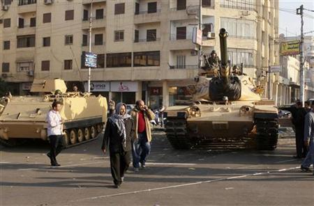Supporters of the Muslim Brotherhood walk past tanks that were just deployed outside the Egyptian presidential palace in Cairo December 6, 2012. At least three tanks are deployed outside the palace on Thursday in a street where supporters and opponents of President Mohamed Mursi had been clashing into the early hours of the morning, a Reuters witness said. REUTERS/Asmaa Waguih (EGYPT - Tags: POLITICS CIVIL UNREST MILITARY)