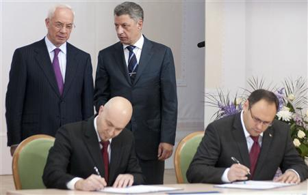 Ukrainian Prime Minister Mykola Azarov (L) and Energy Minister Yuri Boiko (2nd R) talk as Vladislav Kaskiv (R), the head of Ukraine's state investment agency, and a man the state investment agency identified as Jordi Sarda Bonvehi (2nd L) sign what the government said was an agreement to build a liquefied natural gas terminal in Ukraine during a meeting in Kiev in this November 26, 2012 file photo. REUTERS/Stringer/Files