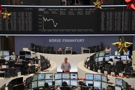 Traders are pictured at their desks in front of the DAX board at the Frankfurt stock exchange December 5, 2012. REUTERS/Remote/Lizza David