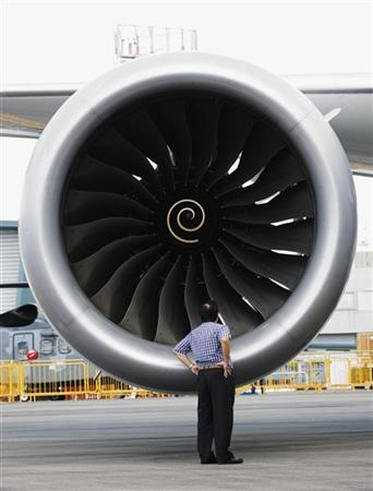 A man looks into one of two Rolls Royce Trent 1000 engines of the Boeing 787 Dreamliner during a media tour of the aircraft ahead of the Singapore Airshow in Singapore February 12, 2012. REUTERS/Edgar Su