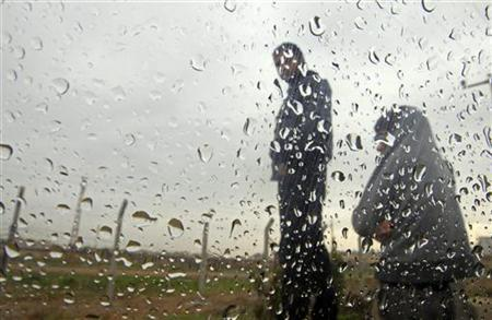 Syrian refugees stand in the rain near the border with Syria, in the Turkish border town of Ceylanpinar, Sanliurfa province December 6, 2012. REUTERS/Laszlo Balogh