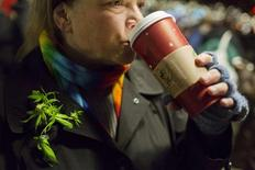 Wearing items representative of the state's historic events, Desiree Moore, a 20-year marijuana activist, takes a sip of her coffee at a marijuana smoke out event in Seattle, Washington December 6, 2012. Hundreds of marijuana enthusiasts huddled near Seattle's famed Space Needle tower on Thursday night with pipes, bongs and hand-rolled joints to celebrate Washington's new status as the first state in the nation to legalize pot for adult recreational use. REUTERS/Jordan Stead