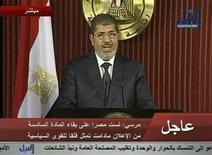 """El presidente egipcio, Mohamed Mursi, invitó a grupos políticos y a otras figuras a reunirse el sábado para sostener un diálogo nacional sobre una hoja de ruta política tras un referendo sobre una nueva Constitución, en una jornada en la que los opositores volvieron a pedir la """"caída del régimen"""". Imagen de Mursi durante una intervención televisada en El Cairo el 6 de diciembre. REUTERS/Nile TV via Reuters TV"""