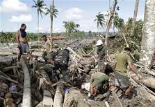 Солдаты разгребают поваленные тайфуном кокосовые деревья в поисках выживших в городе Нью-Батаан 6 декабря 2012 года. Жители южной части Филиппин начали в пятницу хоронить погибших в результате удара мощнейшего тайфуна и вызванного им наводнения, в то время как общие число жертв стихии выросло до 418 человек. REUTERS/Erik De Castro