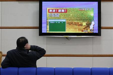 A man scratches his head as he watches television showing live camera footage from Ishinomaki, Miyagi prefecture and an alert sign that reads,''Tsunami! Evacuate!'' at Nagano train station, central Japan December 7, 2012. REUTERS/Yuriko Nakao (JAPAN - Tags: DISASTER)
