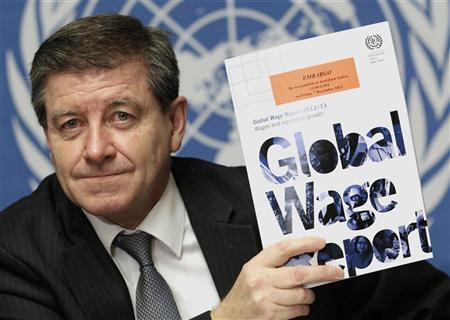 Guy Ryder, Director-General of the International Labor Organization (ILO) poses with a copy of the Global Wage Report after a news conference at the United Nations European headquarters in Geneva December 7, 2012. REUTERS/Denis Balibouse