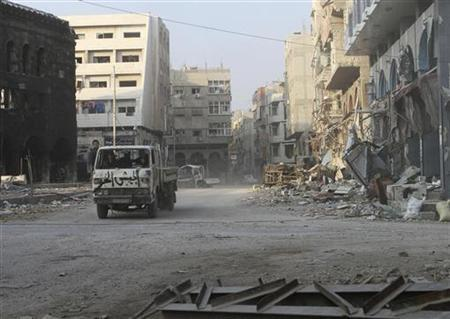 Free Syrian Army members drive past damaged buildings in the Damascus suburb of Douma November 21, 2012. Picture taken November 21, 2012. REUTERS/Moataz al-Qanawati (SYRIA - Tags: CONFLICT POLITICS CIVIL UNREST)