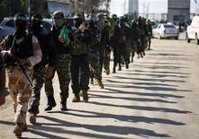 """Palestinos do braço armado do movimento Hamas patrulham rua à espera da chegada do líder do Hamas, Khaled Meshaal, no sul da Faixa de Gaza. Meshaal, vai pisar no território palestino nesta sexta-feira pela primeira vez em 45 anos para um """"comício da vitória"""" na Faixa de Gaza, exibindo a confiança recém-adquirida depois do conflito do mês passado com Israel. 7/12/2012 REUTERS/Mohammed Salem"""