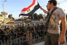 A protester against Egypt's President Mohamed Mursi waves an Egyptian flag in front of Republican Guard soldiers standing behind a barbed wire barricade guarding the presidential palace in Cairo December 7, 2012. REUTERS/Mohamed Abd El Ghany