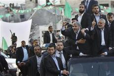 Hamas chief Khaled Meshaal (2nd R) gestures to the crowd as he rides in a car beside senior Hamas leader Ismail Haniyeh (R) in Gaza City December 7, 2012. REUTERS/Ahmed Jadallah