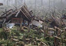 El presidente de Filipinas, Benigno Aquino, declaró el estado catastrófico nacional el sábado, cuatro días después de que el tifón más fuerte que ha vivido el país este año dejara casi un millar de muertos o desaparecidos, principalmente en el sur del país. En la imagen, varias víctimas del tifón a las puertas de su casa destruida en Nuevo Batán el 7 de septiembre de 2012. REUTERS/Erik De Castro