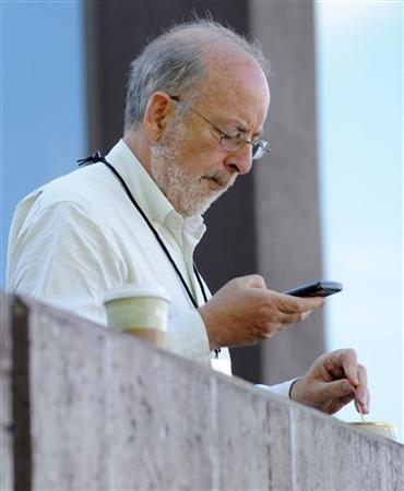 Governor of the Central Bank of Ireland Patrick Honohan uses his cell phone during a coffee break at the Federal Reserve Bank of Kansas City Economic Policy Symposium in Jackson Hole, Wyoming, August 26, 2011. REUTERS/Price Chambers