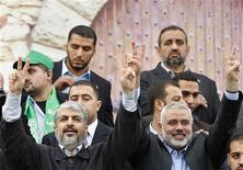"""Hamas chief Khaled Meshaal (L) and senior Hamas leader Ismail Haniyeh flash victory signs upon arrival at a rally marking the 25th anniversary of the founding of Hamas, in Gaza City December 8, 2012. After receiving a hero's welcome on his return from decades in exile, Hamas leader Khaled Meshaal will attend a rally in Gaza on Saturday to mark the founding of his Islamist group and celebrate """"victory"""" over Israel. REUTERS/Mohammed Salem"""