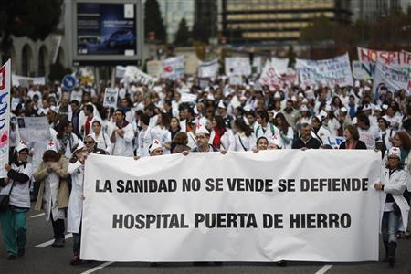 Demonstrators march behind a banner that reads: ''Healthcare is not for sale, we have to defend it. Puerta de Hierro hospital'' during a protest against the local government's plans to cut spending on public healthcare in Madrid November 18, 2012. REUTERS/Susana Vera