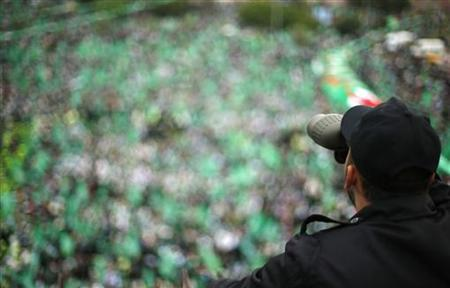 A Palestinian looks through a pair of binoculars as he keeps guard during a rally marking the 25th anniversary of the founding of Hamas, in Gaza City December 8, 2012. REUTERS/Suhaib Salem
