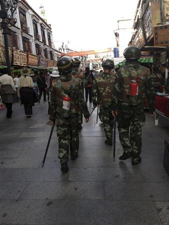 In this undated handout photo released by The International Campaign on for Tibet (ICT) on December 7, 2012, paramilitary policemen, equipped with fire extinguishers, patrol a street of Lhasa. As the number of self-immolations in restive Tibetan regions rises sharply, Beijing appears to be tightening rules against the anti-China protests despite hopes the new leadership may take a softer line against Tibet. REUTERS/Handout/The International Campaign for Tibet