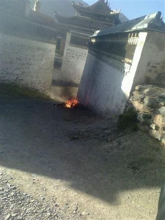 In this handout photo released by The International Campaign for Tibet (ICT) on December 7, 2012, the body of Dhondup is seen still in flames near a side wall of Serkhang temple at Labrang Tashikyil monastery, Gannan Tibetan Autonomous Prefecture, Gansu province, October 22, 2012. As the number of self-immolations in restive Tibetan regions rises sharply, Beijing appears to be tightening rules against the anti-China protests despite hopes the new leadership may take a softer line against Tibet. REUTERS/Handout/The International Campaign for Tibet